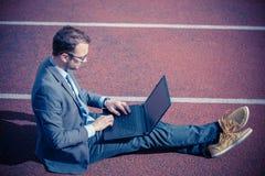 坐赛马跑道和研究膝上型计算机的商人 免版税图库摄影