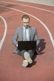 坐连续轨道和研究膝上型计算机的商人 图库摄影