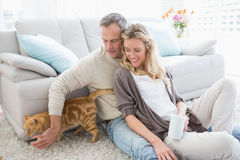坐逗人喜爱的夫妇食用咖啡和宠爱他们的猫 免版税库存照片