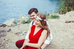 坐通过湖拥抱的夫妇 库存照片