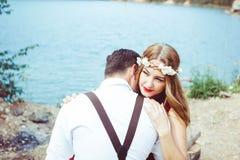 坐通过湖拥抱的夫妇 库存图片