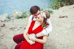 坐通过湖拥抱的夫妇 免版税图库摄影
