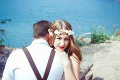 坐通过湖拥抱的夫妇 免版税库存图片