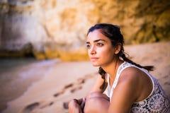 坐金黄沙子在海滩在岩石附近和看海洋的Potrait拉丁女孩 夏天职业 免版税库存照片