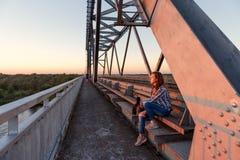 坐钢桥梁设计在船坞和注视着日落的青少年的女孩流浪汉 免版税库存图片