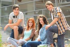 坐长凳前面学院的小组学生 库存图片