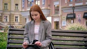坐长凳和使用片剂,城市街道背景的夹克的年轻俏丽的姜妇女 股票视频