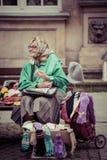 坐长凳和卖手套的老妇人 库存图片