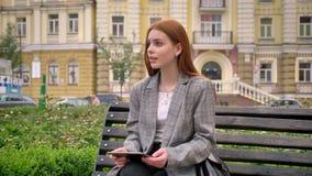 坐长凳和拿着片剂,城市街道背景的夹克的年轻美丽的姜妇女 股票视频