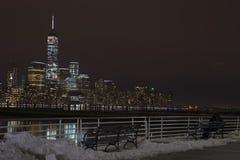 坐长凳和看在曼哈顿夜地平线的恋人夫妇 免版税库存图片