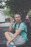 坐长凳户外和使用智能手机的愉快的年轻英俊的人 巴厘岛,印度尼西亚热带海岛  图库摄影