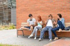 坐长凳校园外的学生朋友 免版税图库摄影