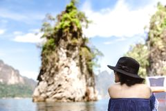 坐长尾巴小船和享受看法的妇女的后部 库存图片