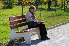 坐长木凳和读一本书的资深妇女在公园在伏尔加格勒 免版税图库摄影