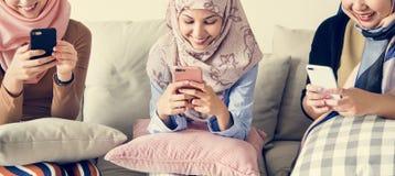 坐长沙发和使用巧妙的电话的小组伊斯兰教的女孩 免版税库存照片