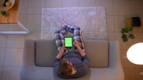 坐长沙发和使用应用程序的年轻便服男性看着电视特写镜头顶面射击在片剂作为 影视素材