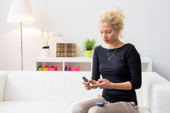 坐长沙发和使用糖尿病针的妇女 免版税图库摄影