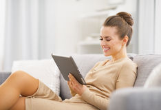 坐长沙发和工作在片剂个人计算机的愉快的少妇