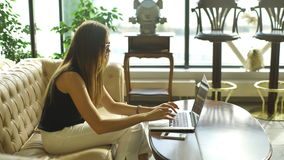 坐长沙发和工作在计算机的美丽的女孩 股票录像