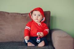 坐长沙发和拿着橄榄球足球玩具的孩子 库存图片