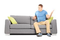 坐长沙发和猛烈地摇摆他的手的恼怒的人 免版税图库摄影