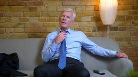 坐长沙发和疏松他的领带的老白种人商人看着电视特写镜头画象在工作以后户内  股票录像