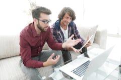 坐长沙发和看膝上型计算机屏幕的两个人 图库摄影