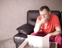 坐长沙发和研究他的膝上型计算机,copyspace的人 免版税库存照片