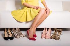 坐长沙发和选择什么鞋子的妇女佩带 库存照片
