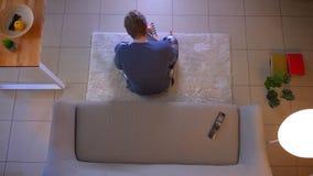 坐长沙发和采取在笔记本的年轻便服男性看着电视特写镜头顶面射击笔记 影视素材
