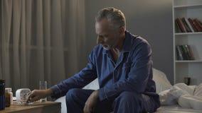 坐长沙发和采取止痛药,健康问题的哀伤的年迈的人 免版税库存图片