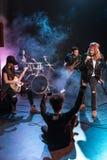 坐阶段和拍摄摇滚乐队的妇女 免版税库存图片