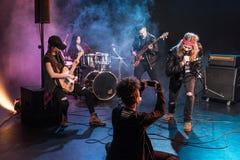 坐阶段和拍摄摇滚乐队的妇女 图库摄影