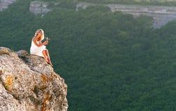 坐顶部妇女的美丽的山 库存照片
