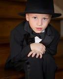坐顶部无尾礼服的男孩帽子 库存照片