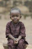 坐令人敬畏的骄傲的非洲的男孩户外 免版税库存图片