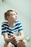 坐洗手间的年轻白肤金发的男孩 免版税库存照片