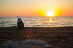 坐他的腰臀部分和接触沙子的孩子 免版税库存图片