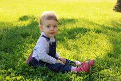 坐绿草在公园和微笑在夏天愉快的天的可爱的婴孩 库存图片