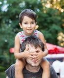 坐紧跟在他的父亲后面的婴孩 免版税库存图片