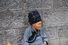 坐年长苗族的妇女外面 图库摄影