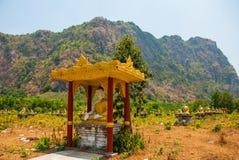 坐Buddhas的许多雕象,在与山的美好的风景中在晴天 Hpa-An,缅甸 缅甸 免版税图库摄影