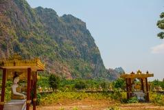 坐Buddhas的许多雕象,在与山的美好的风景中在晴天 Hpa-An,缅甸 缅甸 图库摄影