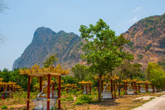 坐Buddhas的许多雕象,在与山的美好的风景中在晴天 Hpa-An,缅甸 缅甸 免版税库存照片