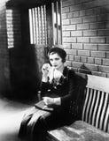 坐n的少妇在牢房前面的一条长凳(所有人被描述不更长生存,并且庄园不存在 供应商 免版税图库摄影