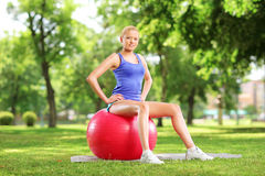 坐pilates球和看c的年轻女运动员 免版税库存图片