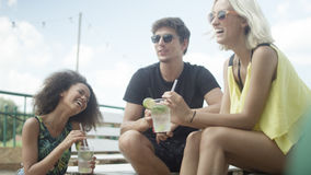 坐sunbeds在伞下和享受假期的年轻美丽的混合的族种朋友 库存图片