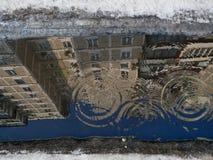 水坑,从雨投下水的表面,灰色大厦的镜象上的圈子与窗口的,沿水坑 免版税库存图片