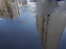 水坑:大海的表面上是被反射的白色许多楼层大厦,在那里左下角是空的空间为 免版税库存照片