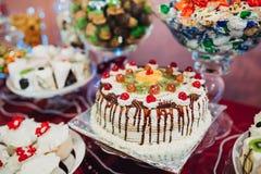 结块与黄油奶油和倒的巧克力的装饰的樱桃 免版税库存图片